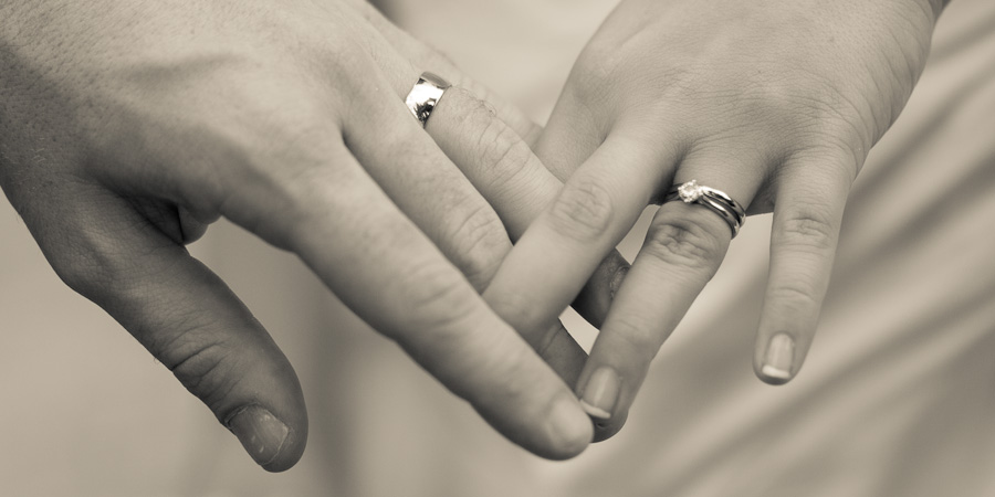 Bride and groom with fingers intertwined showing off their new wedding rings