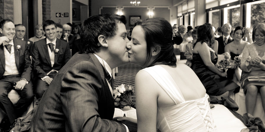 Bride and groom sneak a quick kiss after their wedding ceremony in Rochdale