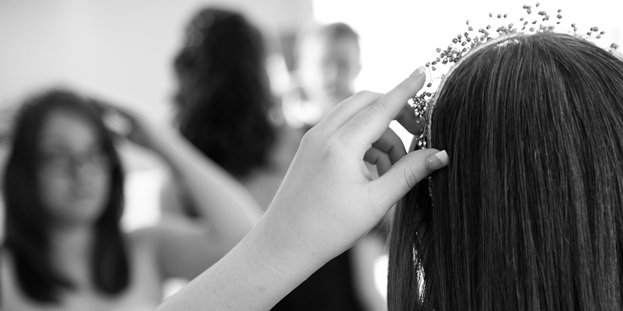 A bride looks into the mirror as she prepares for her wedding in Manchester Town Hall by putting on her tiara