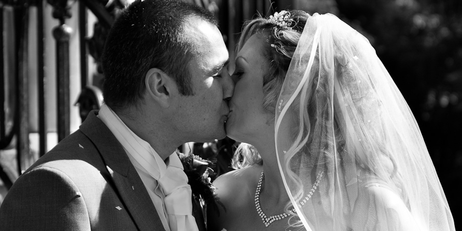 Bride and groom celebrate with a kiss as they pose for their wedding photography in Manchester