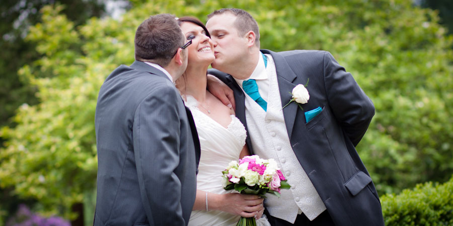The bride gets a kiss from the two best men at a wedding